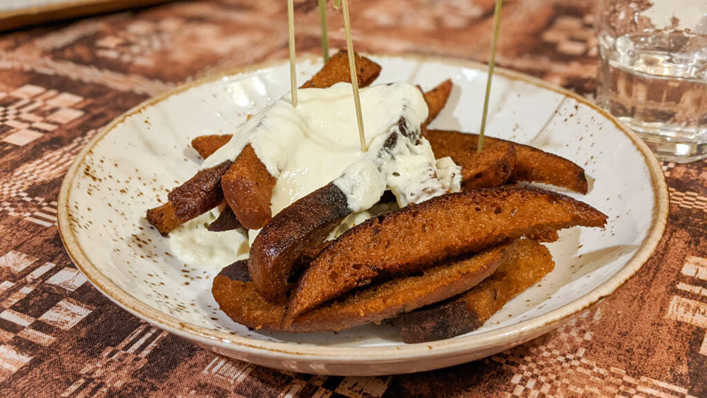 Kepta Duona - fried bread sticks smothered in cheese sauce on a plate