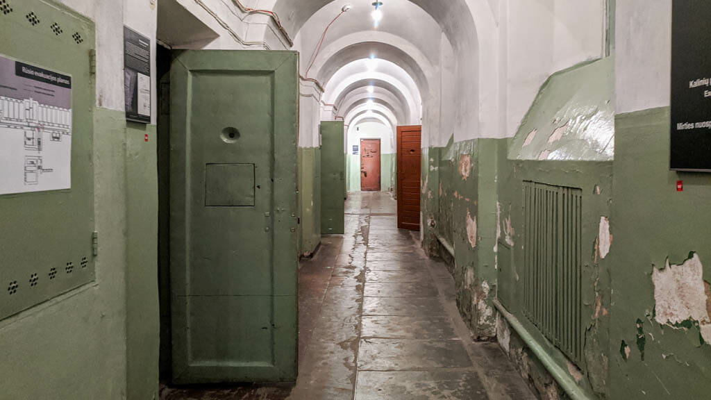 Prison hall way with green doors and walls and white ceiling at the Museum of Occupations and Freedom Fights