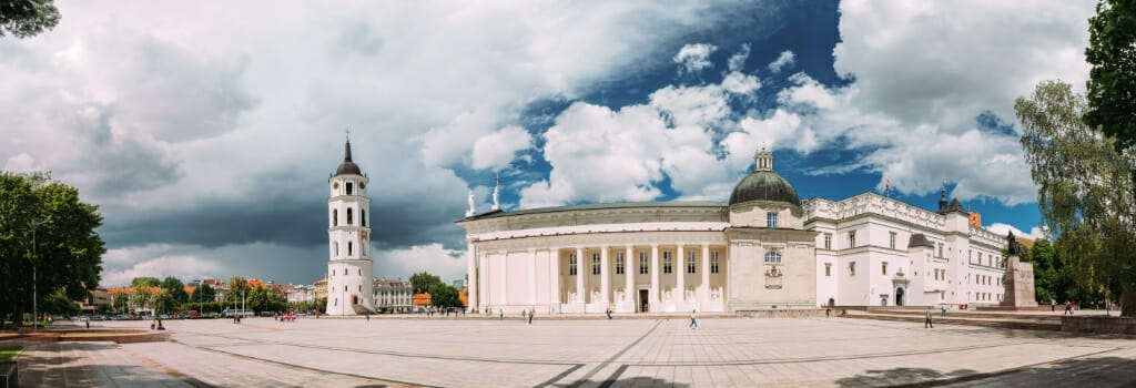 Vilnius Cathedral Square with white church buildings and tower and a stormy dark sky