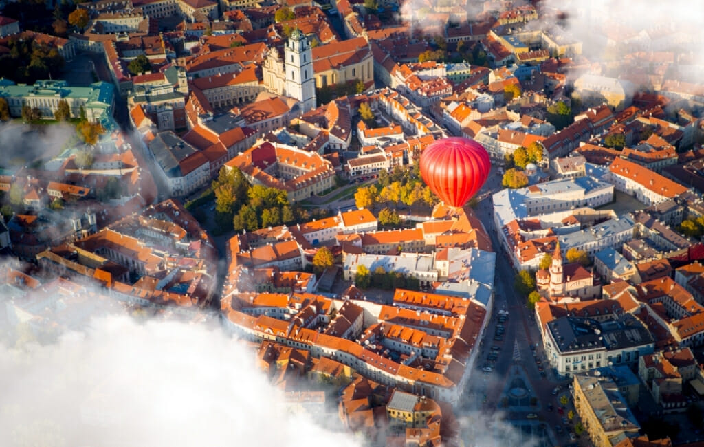 Aerial photo of Vilnius through the clouds with a red hot air balloon flying over the city