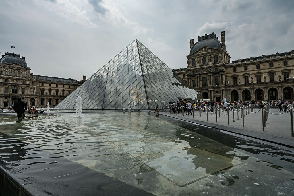 Glass pyramid and water pool in front of Louvre Paris - Things To do in Paris