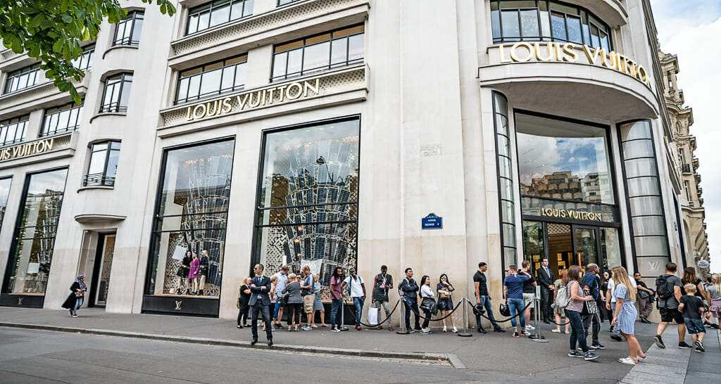 People standing in line in front of Louis Vuitton Store on Champs Elysées in Paris