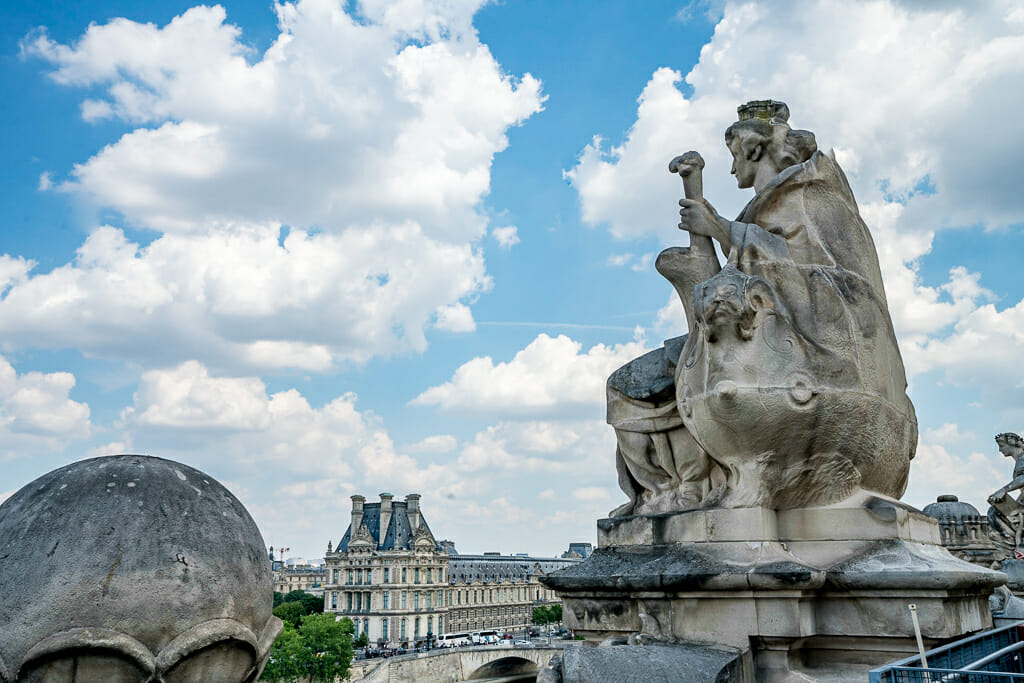 Stone sculpture on the roof of Musée d'Orsay with view of the Louvre in the background
