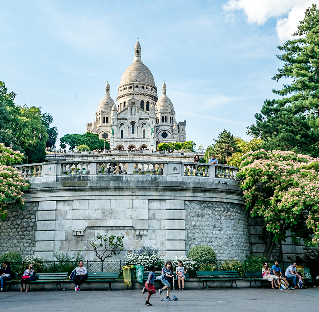 view of white church with domes Sacré-Coeur in Montmartre on a sunny day