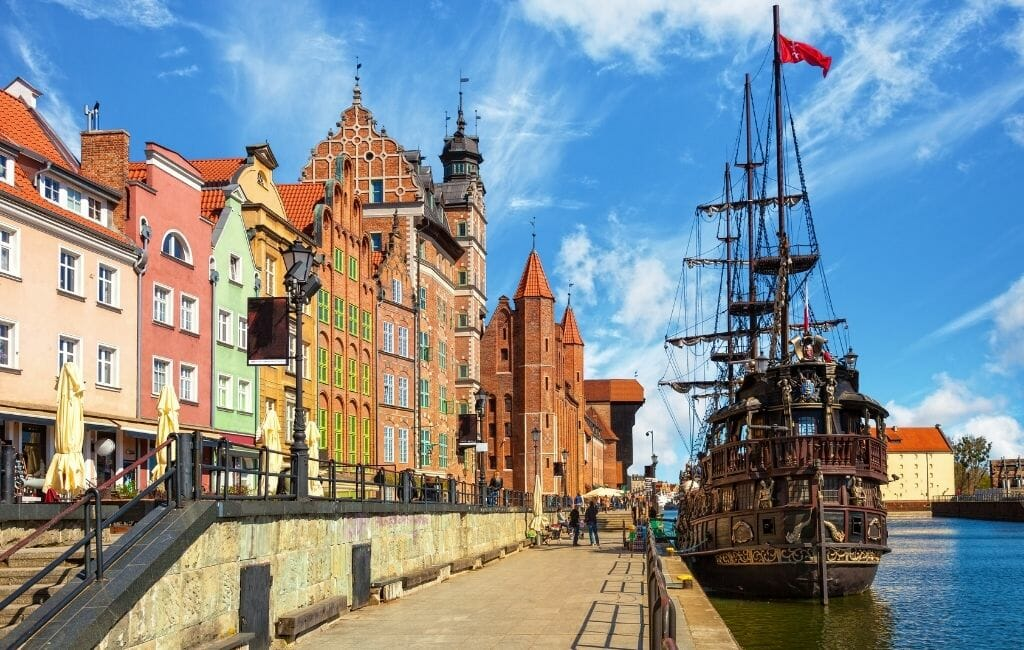 Historic wood sailboat anchored on the waterfront in Gdansk with colorful row houses