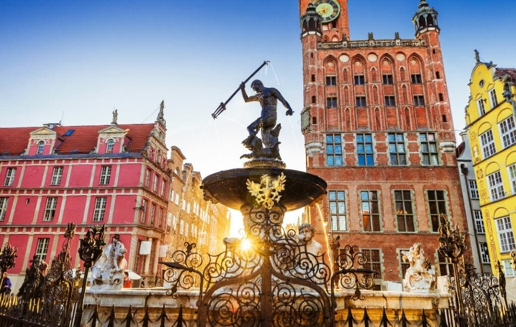 Fountain on the main square in Gdansk with red, orange, and yellow historic buildings in the background