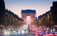 Champs Elysees with traffic in the foreground and Arc de Triomphe in the background during sunset