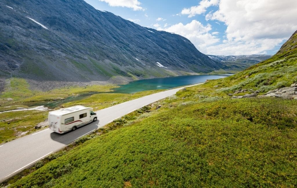 White Rv driving on a road in Norway through a Valley