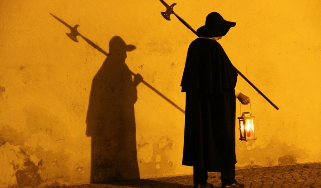 Nightwatchman in a coak and with a spear and lanter casting a shadow on an orange wall in Rothenburg ob der Tauber