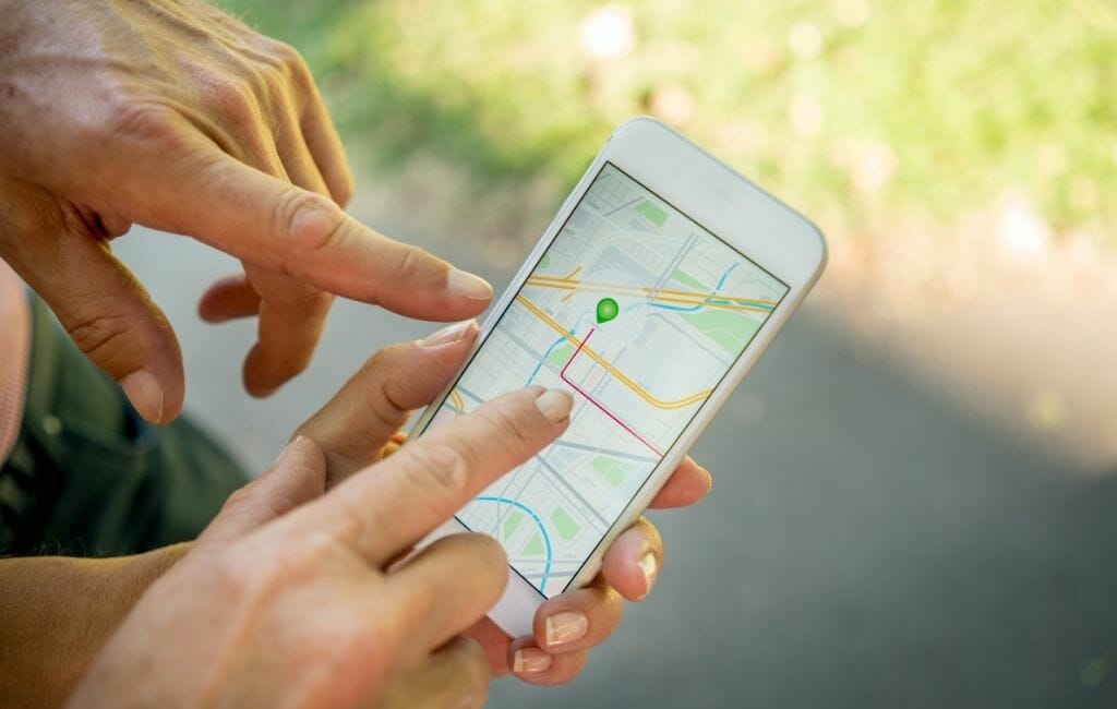 closeup of two hands holding a phone with a map on the screen