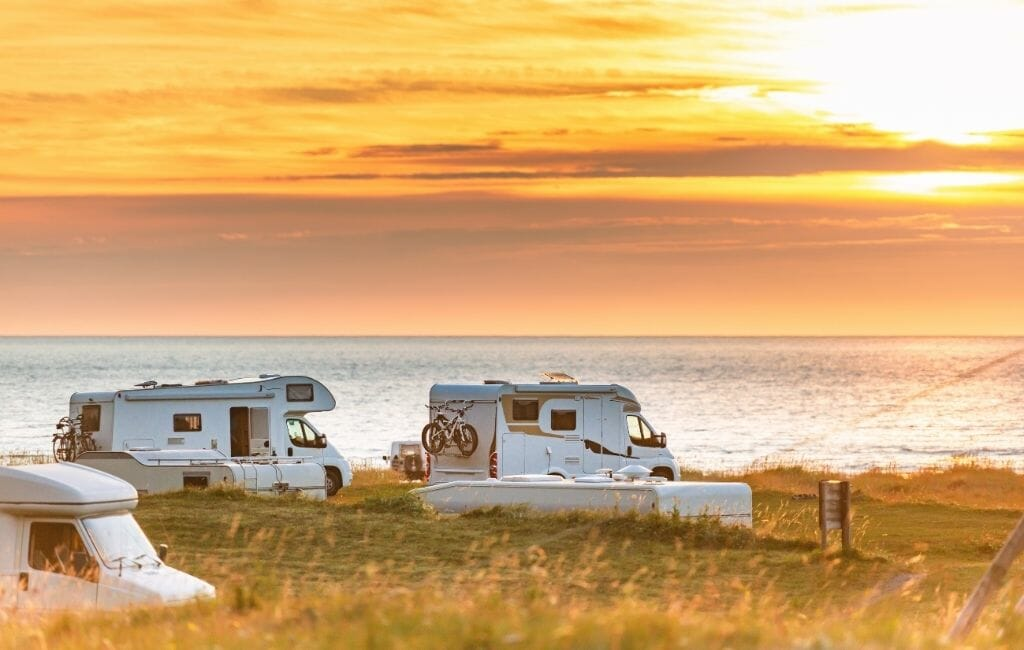 3 white RVs parked by the ocean during sunset