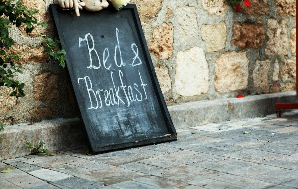 old stone wall with antique sign that reads:Bed and Breakfast in chalk
