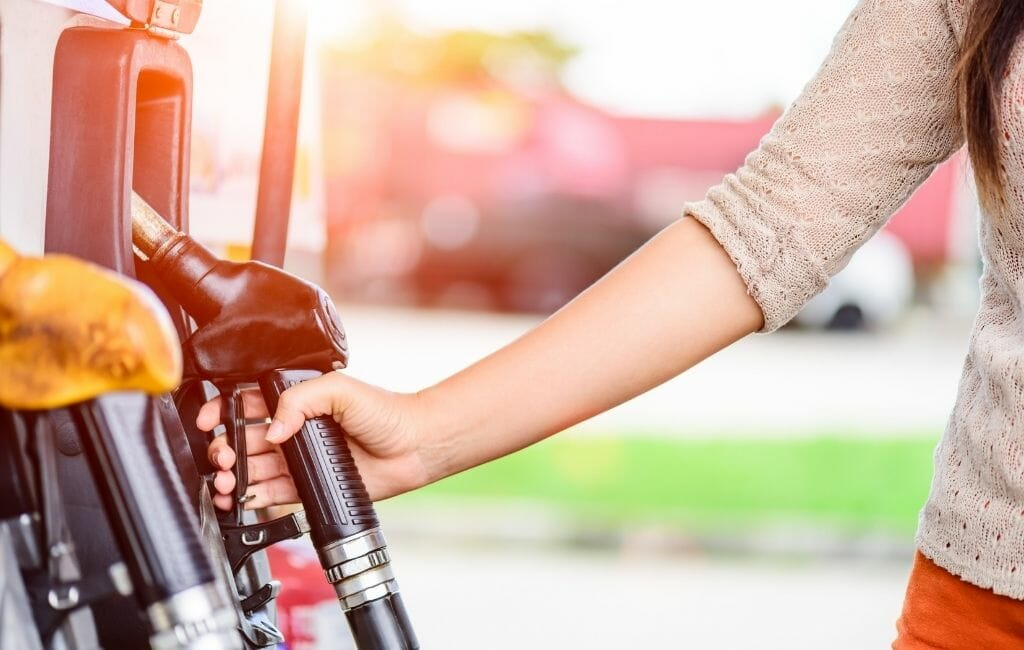 Female arm reaching for a gas pump at a gas station