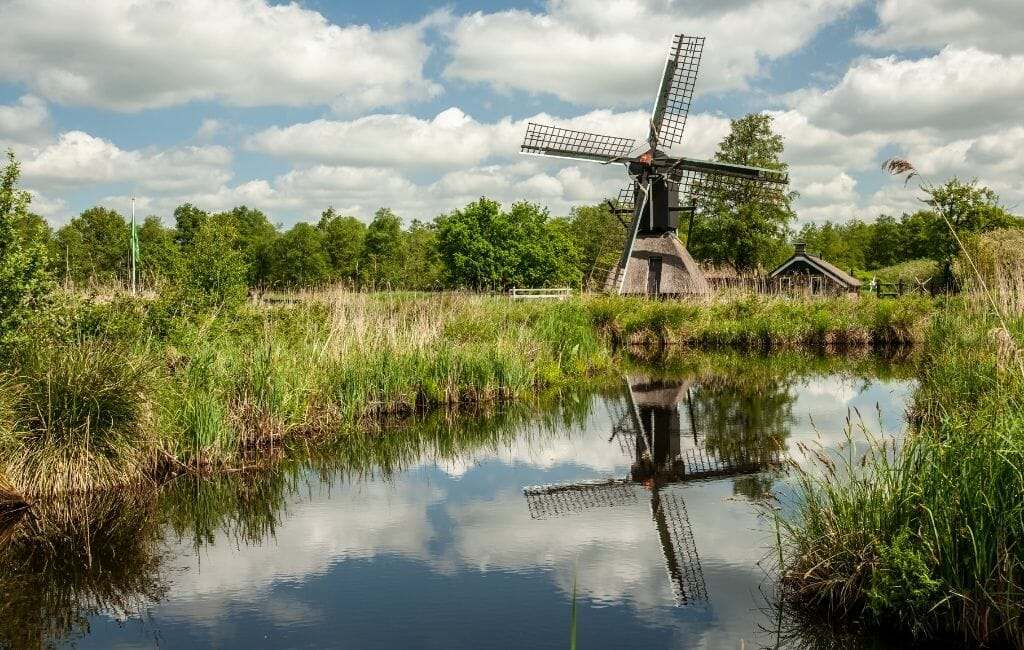 Small wooden windmill on a grass meadow next to canal near Giethoorn