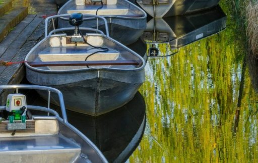 Several small boats tied up on a canal in Giethoorn called Whisperboats