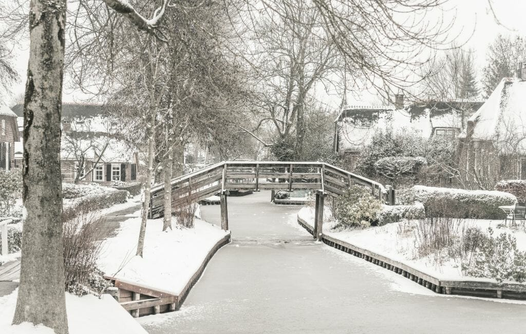 Giethoorn in Winter with snow - canal with wooden bridge and historic houses covered with a blanket of snow