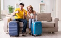 couple sitting on couch with suitcases in front of them